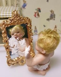 Porzellanpuppe - Baby sitzt vor Spiegel und verziert diesen und sich selbst mit Handcreme