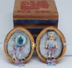 Little boy doll and tambourine in walnut shell