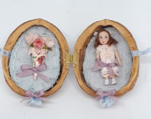 Little doll and paper cone with roses in hinged walnut shell